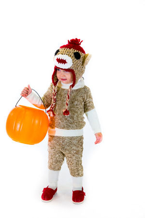 trick or treating: A two year old dressed up in a sock monkey halloween costume and ready to go out and trick-or-treat in the neighborhood for the holiday. Stock Photo