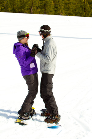ski runs: A couple snowboards down some groomed ski runs at a mountain resort.
