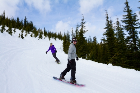 ski runs: A couple snowboards down some groomed ski runs at a mountain resort.