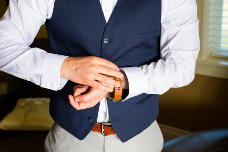navy blue suit: A groom fastens his watch on his wrist while getting ready for a wedding day celebration.