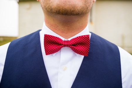 bowtie: A fashionable groom wears a red and white bowtie with a navy blue vest on his wedding day.