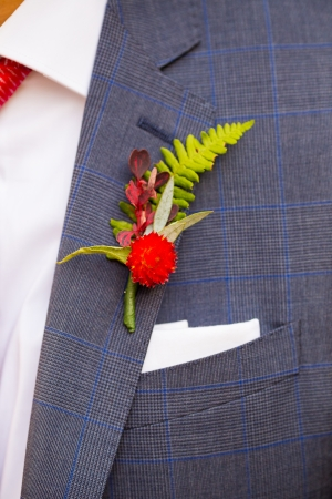 A groom wearing a boutineer on his wedding day made from natural flowers and plants. photo