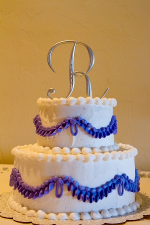 topper: A cake topper with the letter R on it on this white and purple cake indoors. Stock Photo