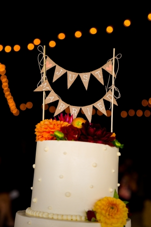 topper: A handmade cake topper has flags that say just married on it above the wedding cake at this reception party. Stock Photo