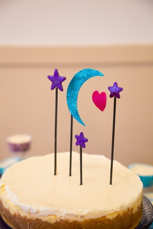 topper: This handmade cake topper has a moon, heart, and stars on it above a wedding cheesecake.