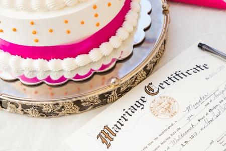 A wedding cake sits next to the bride and groom marriage certificate at this ceremony and reception.