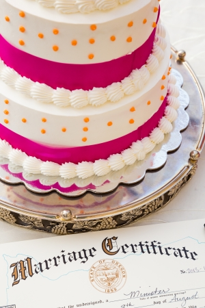 marriage certificate: A wedding cake sits next to the bride and groom marriage certificate at this ceremony and reception.