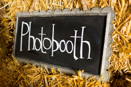 Decor at this wedding includes chalkboard signs that say photobooth or photo booth to indicate its location at the reception.