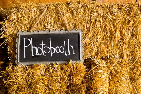 Decor at this wedding includes chalkboard signs that say photobooth or photo booth to indicate its location at the reception. photo