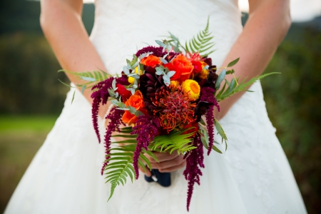 A bride in a white wedding dress holds her bouquet of flowers on her wedding day.