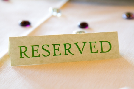tage: A name tage at a wedding says Reserved to hold a spot for the bride and groom and their important family at a ceremony and reception.