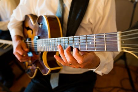 A guitar player is playing his guitar at a wedding for the guests during the reception.