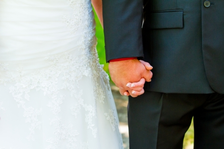 A bride and groom share a special moment while holding hands on their wedding day.