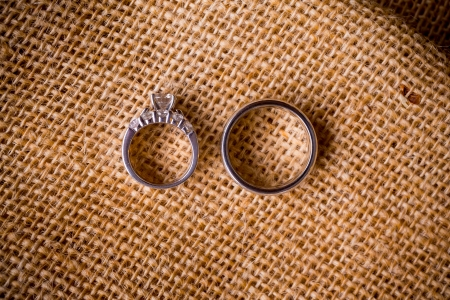 A burlap sack cloth is used to set rings on for a wedding day closeup detail color image. photo