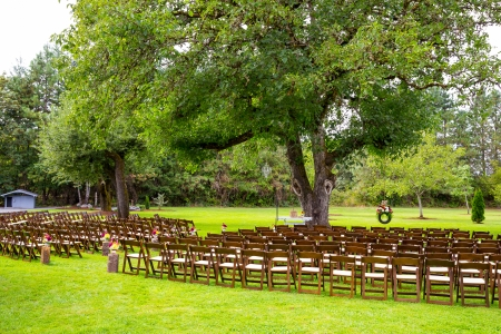 venue: A beautiful country wedding venue location is setup for the ceremony with chairs and decorations awaiting the arrival of guests. Stock Photo