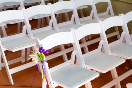 venue: White wedding venue chairs are setup and ready in rows waiting for guests to arrive for the ceremony. Stock Photo