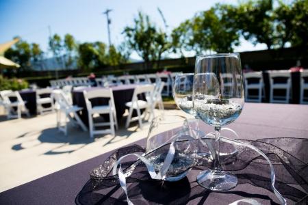 Glazen wijn zijn de blikvangers van dit elegante luxe bruiloft buiten op een wijngaard. Stockfoto