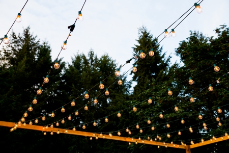 venue: At a wedding reception lights are hung in strands to create a night illuminated dance floor for this outdoor event at night. Stock Photo