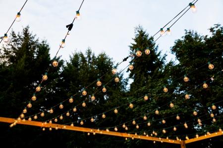 Op een bruiloft receptie lichten worden opgehangen in strengen om een ??nacht verlichte dansvloer te creëren voor dit outdoor evenement in de nacht. Stockfoto - 24133961