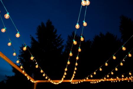 Op een bruiloft receptie lichten worden opgehangen in strengen om een nacht verlichte dansvloer te creëren voor dit outdoor evenement in de nacht. Stockfoto