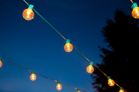 At a wedding reception lights are hung in strands to create a night illuminated dance floor for this outdoor event at night. Stock Photo