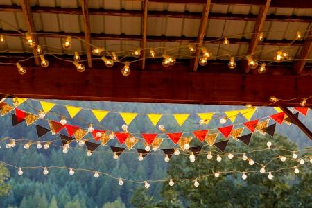 결혼식 피로연에서 빛은 밤에이 옥외 사건을위한 야간 조명 댄스 플로어를 만들기 위해 물가에 매달려 있습니다. 스톡 콘텐츠