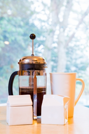 Coffee is being made in a french press along with cream and sugar on the kitchen counter early in the morning. Фото со стока