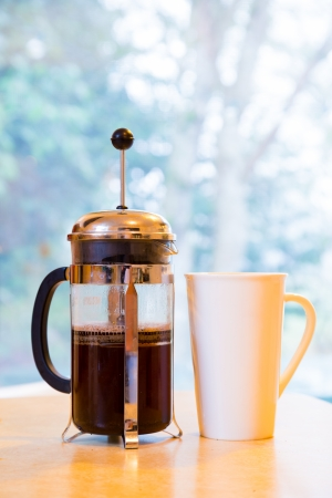 Coffee is being made in a french press along with cream and sugar on the kitchen counter early in the morning. Stock Photo
