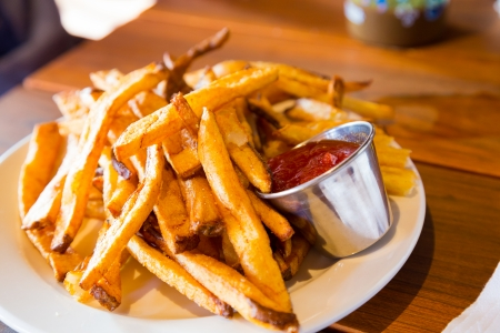 dining out: Ketchup or catsup is served next to some potato fries at a restaurant while dining out. Stock Photo