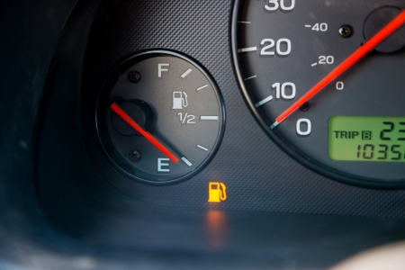 refuel: A gas guage in a car reads empty and shows the warning light to let the driver know they are out of gas and need to refuel.