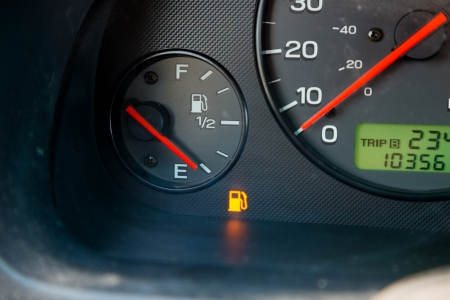 A gas guage in a car reads empty and shows the warning light to let the driver know they are out of gas and need to refuel.