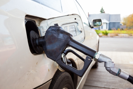 octane: A gas pump is pumping gas into this car at the gas station while refueling. Stock Photo