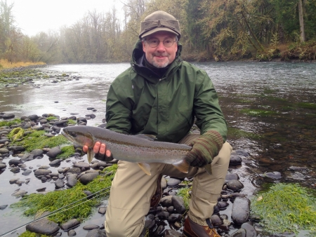 An experienced fly fisherman is holding a steelhead trout that is a trophy fish on the banks of a river in winter. This man is fly fishing for recreation. photo