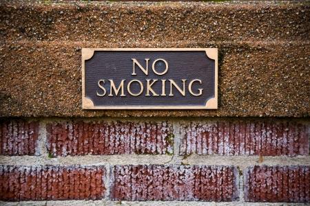 ordenanza: Muestra de no fumadores en el ladrillo fuera de una biblioteca en Oregon que muestra las reglas de ordenamiento de la ciudad.
