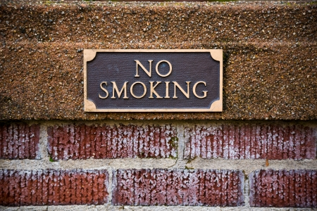 ordinance: No smoking sign on brick outside of a library in Oregon showing the city ordinance rules. Stock Photo