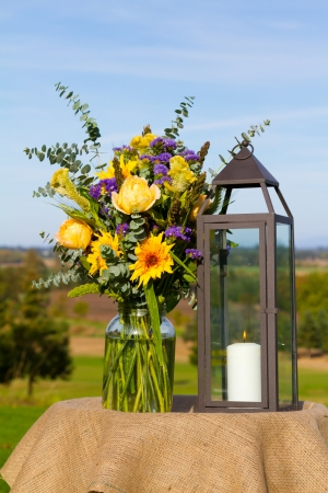 Flowers and candle lanterns are used as the center piece decor at this outdoor wedding venue in summer in oregon. Stockfoto
