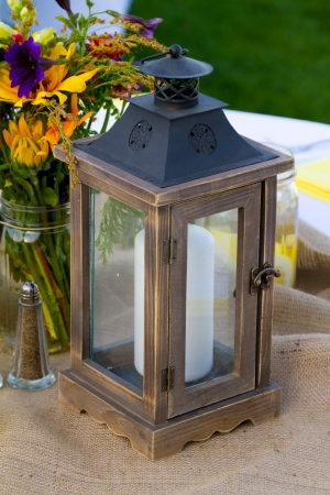 decor: Flowers and candle lanterns are used as the center piece decor at this outdoor wedding venue in summer in oregon. Stock Photo