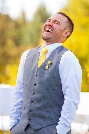 Een knappe bruidegom ziet er gelukkig op zijn trouwdag in grijs en geel.