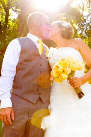smooching: A bride and groom pose for a casual portrait on their wedding day outdoors in the summer in oregon. Stock Photo