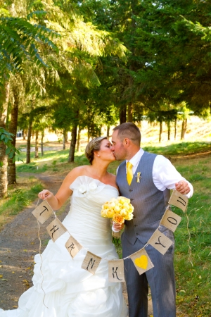 hitched: A bride and groom hold a banner of burlap that reads thank you so they can use it later for their thank you cards.