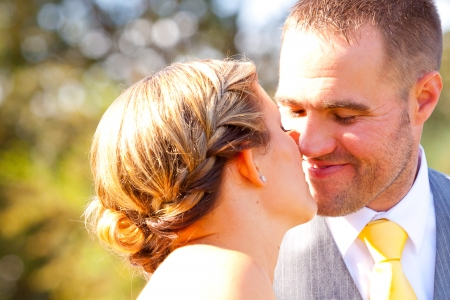 smooching: A bride and groom looking beautiful and handsome on their wedding day outdoors for a portrait session.