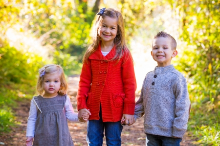 Three children stand together outdoors for a family Christmas holidays photo of the two girls and one boy.
