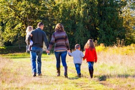 Nucleaire gezin van vijf mensen, waaronder een moeder vader en drie kinderen staan samen in openlucht voor deze familie foto.