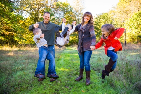 nuclear family: Nuclear family of five people including a mother father and three children stand together outdoors for this family picture.