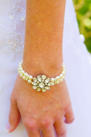 Bride hand and wrist with a pearl bracelet and jewels on it for her wedding day. photo
