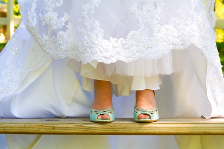 stilletto: Blue wedding shoes shown to the camera by the bride as she lifts up the bottom of her dress on her wedding day.