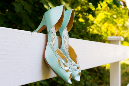 Tiffany blue wedding shoes with heels are hanging on a white fence before the bride puts them on for her wedding ceremony.