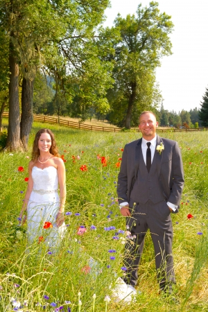 Bride and groom pose for a portrait on their wedding day outdoors at a country venue looking happy and in love together. photo