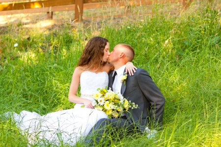 smooching: Bride and groom pose for a portrait on their wedding day outdoors at a country venue looking happy and in love together. Stock Photo