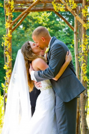 smooching: Kiss shared by the bride and groom during their wedding ceremony in front of guests with the officiant out of focus and unrecognizable .